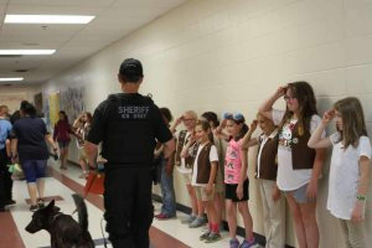 Osceola County Sheriff's Department Sgt. Mark Moore existed the gymnasium with K-9 partner Chase as the local Girl Scout troop salutes each of the everyday heroes in attendance.