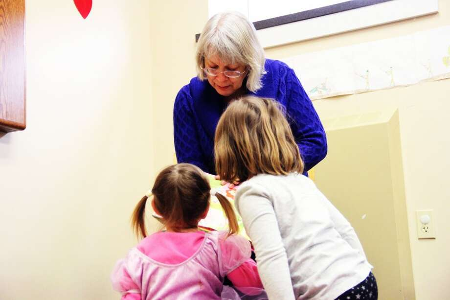 YOUNG LISTENERS: Two children not yet old enough for school enjoy hearing Candy Derevage — known as Mrs. D — read a story. Derevage has read to many children in the Reed City community through her 20 years at Reed City Library. (Herald Review photo/Sarah Neubecker)