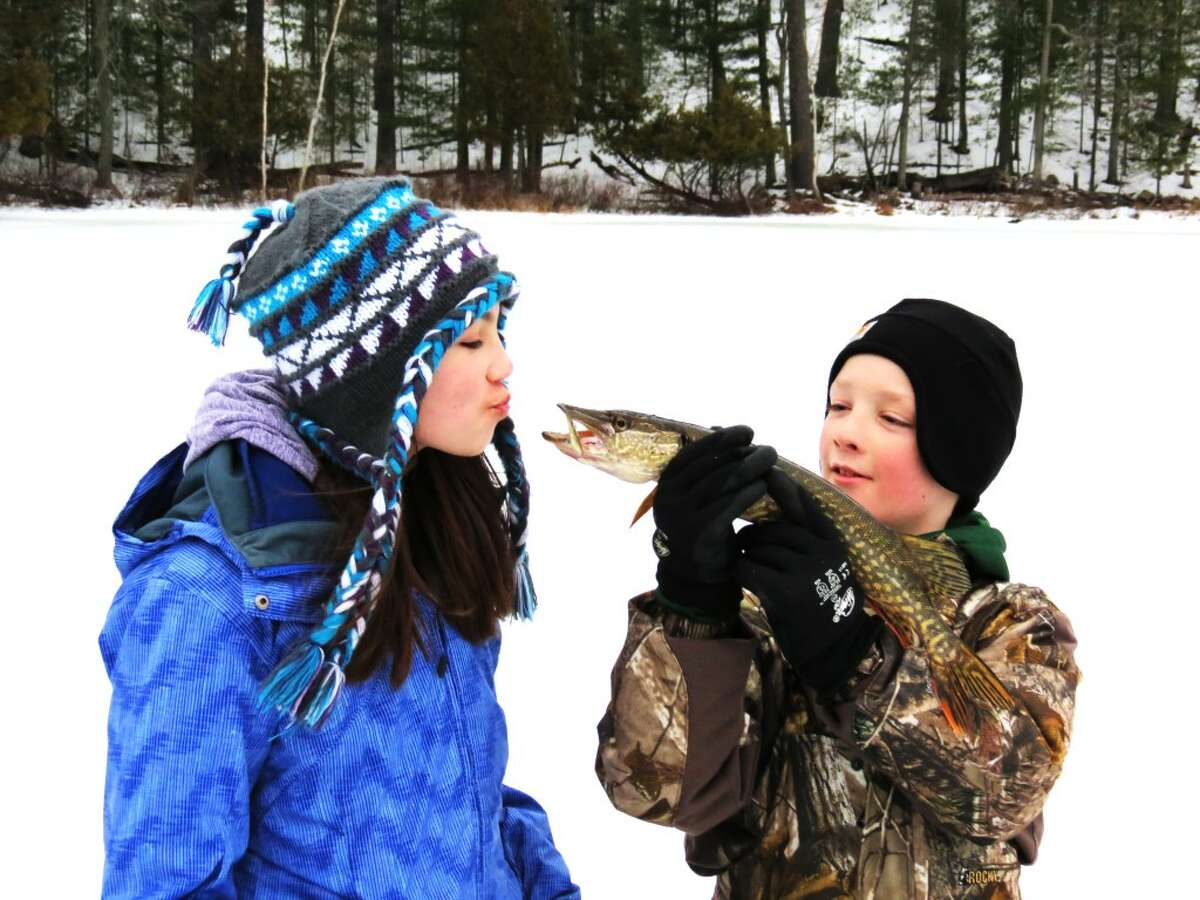 KISSING A FISH: Hannah Hill, of LeRoy, prepares to kiss a pike that she caught on a tip-up on a lake in Irons recently. Her brother Luke is holding it up for her. (Courtesy photos)