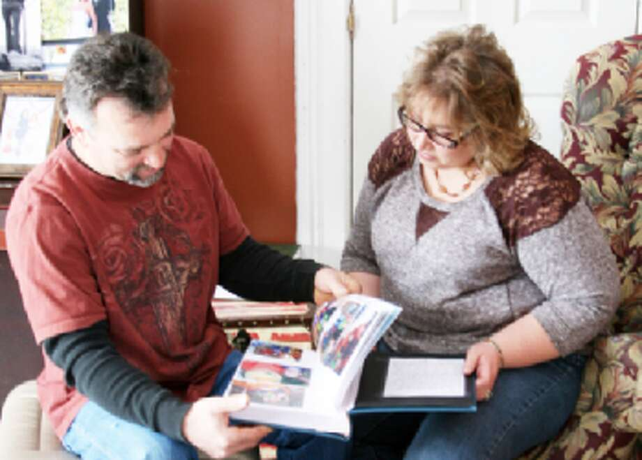 """PART OF THE FAMILY: Gordon and Angie Tower look through the """"life book"""" they made for their 4-year-old foster child they are in the process of adopting with the help of Eagle Village's foster care program. The village is celebrating the one-year anniversary of a facility they use to instruct parents of foster care children. (Herald Review File Photo)"""