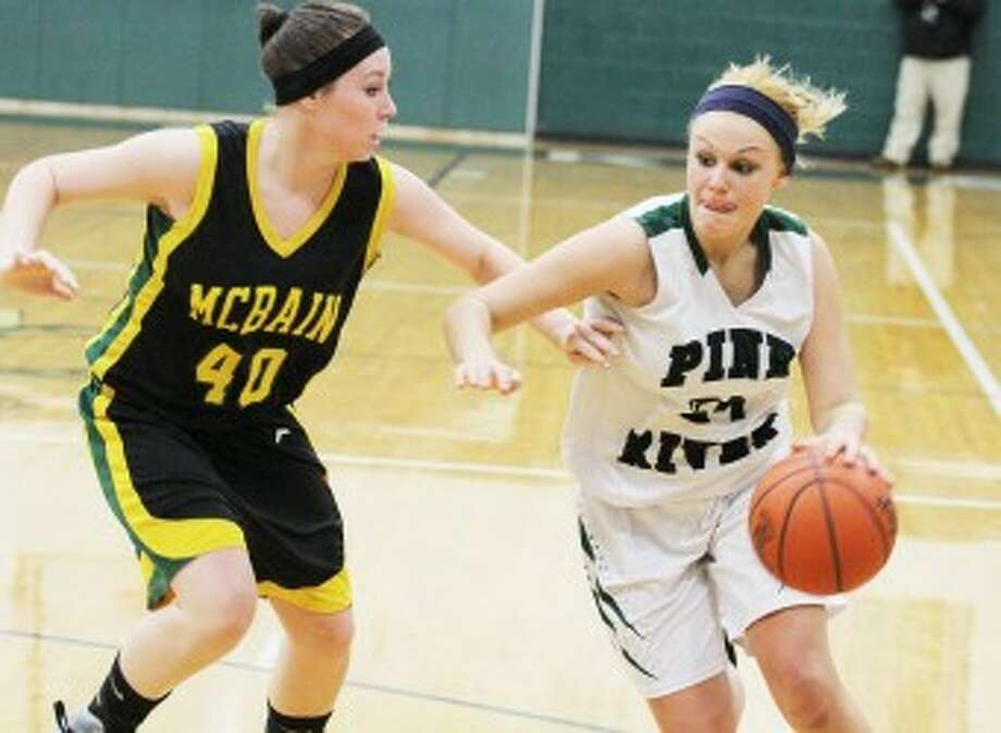 DRIVING: Pine River's Haley Raymond (right) drives to the basket against McBain during Friday's district final. The Bucks won the game 54-32 to claim their second district title in three years. (Pioneer photo/Martin Slagter)