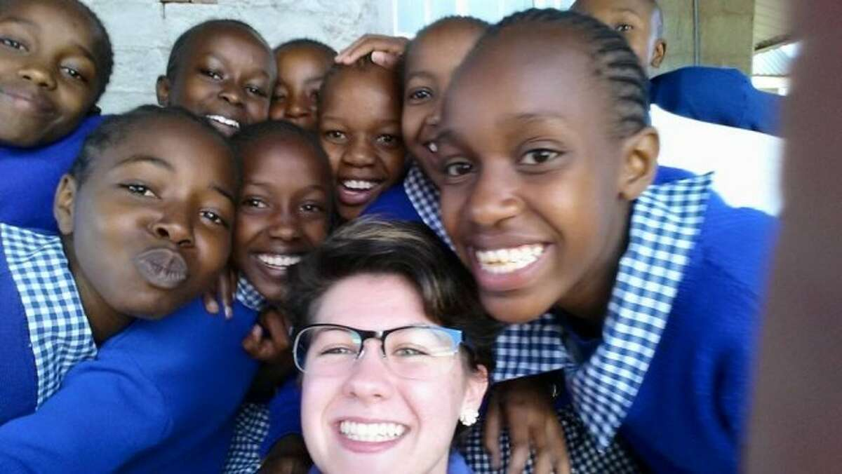 SELFIE: Suzanna Johnson and a group of school children pose for a picture. Johnson helped educated children about dental hygiene, as well as assisting dentists with procedures. Throughout four days of the clinic, 678 children received dental work.