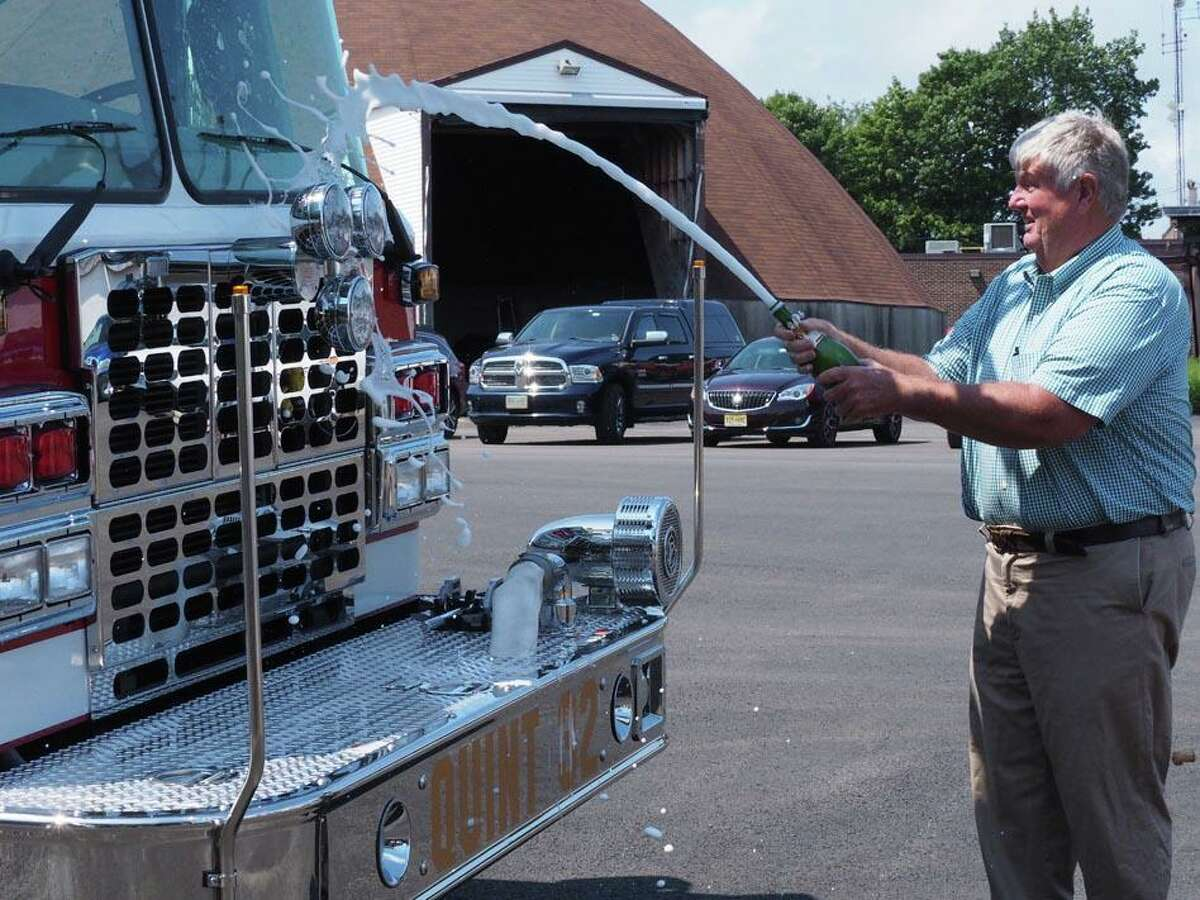 First Selectman Jim Zeoli dedicates the truck by spraying it with champagne.