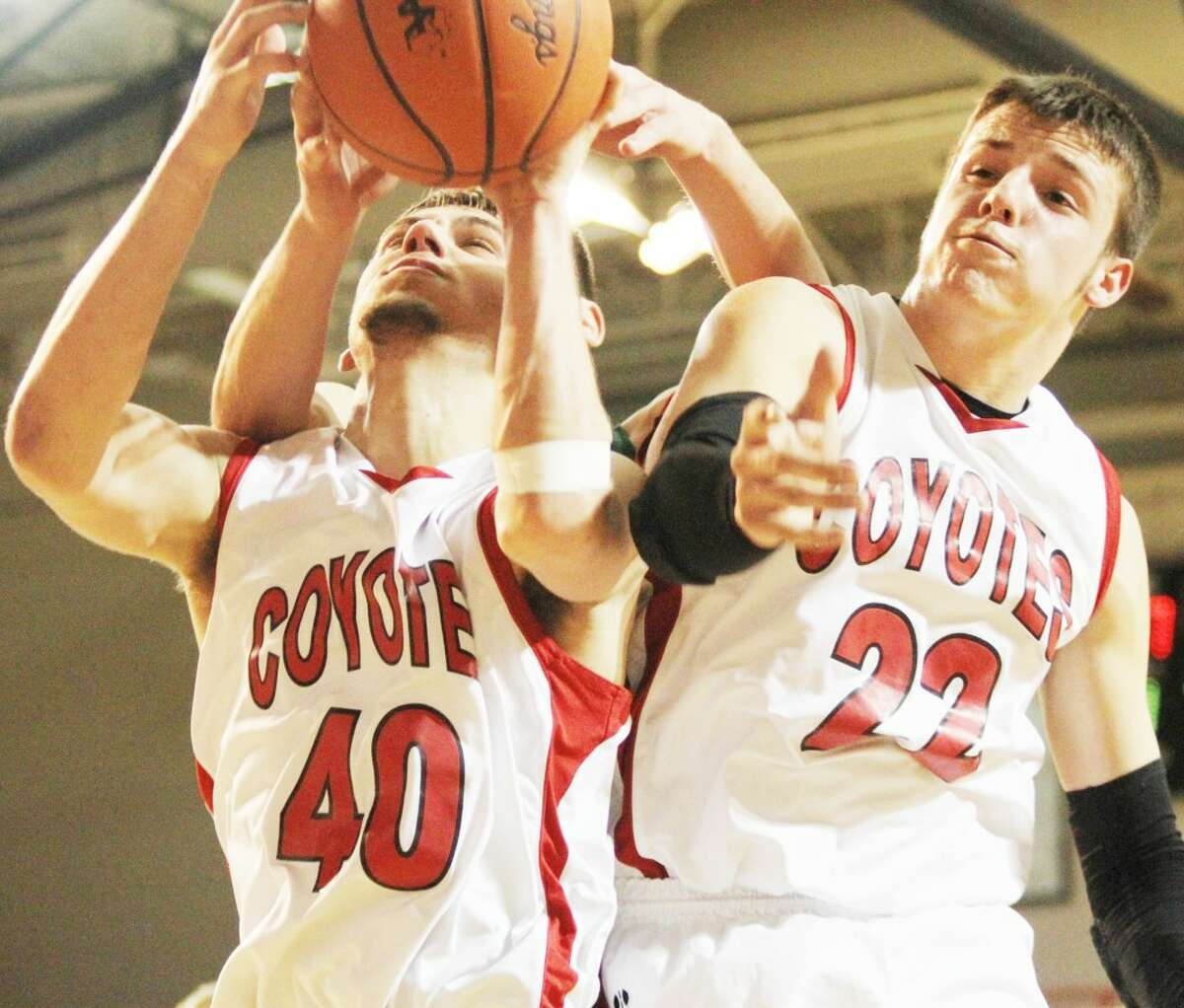 UP FOR GRABS: Reed City's Jake Vincent (left) and Kyle Wright battle for a rebound against Clare during the the Class B district semifinal. (Herald Review photo/Bob Allan)