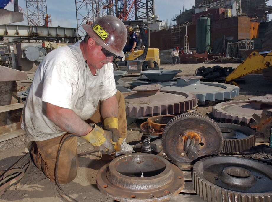 Todd Myers, 40, of Raymond, Miss., works on parts of the elevating units for 'Hercules Rig 26', which sits behind him at R & R Fabricators in Sabine Pass on Friday morning. The 'jack-up' drilling rig is being refurbished to handle almost twice its original capacity in preparation for shipping overseas. The rig is part of a continuing migration of shallow water 'jack-up' drilling rigs out of the Gulf of Mexico and to international locations where they can demand a higher price for their services. © 2007 PHOTO/SCOTT ESLINGER        MARCH 30, 2007 Photo: Scott Eslinger, Freelance / For The Chronicle / Freelance