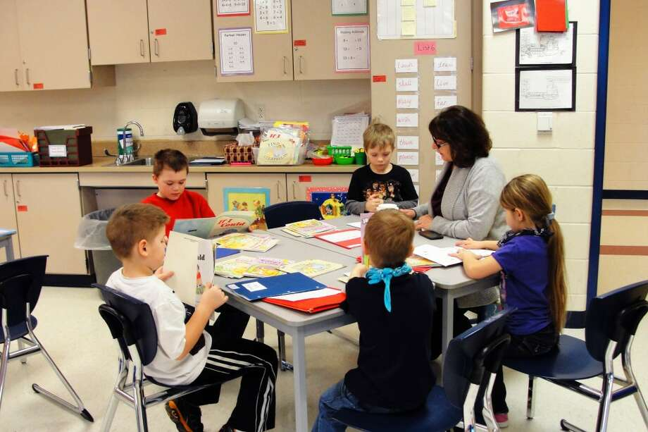 READ ALONG: Evelyn Webster reads with Jackie Ringler's first grade class. (Courtesy photo)
