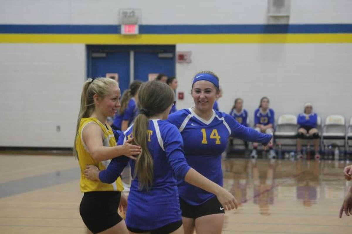 Evart volleyball team celebrates a point.
