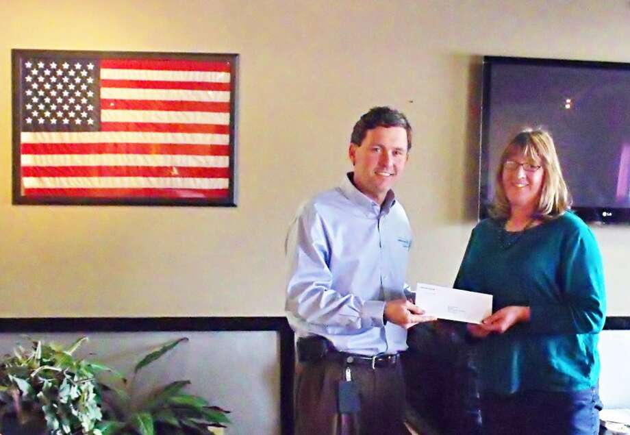 DONATIONS: Jeff Mayes, area manager for Consumers Power turns over his company's donation in support of ongoing chamber projects to Evart chamber past president, Connie Douglas, at last week's chamber meeting. (Herald Review photo/Jim Crees)