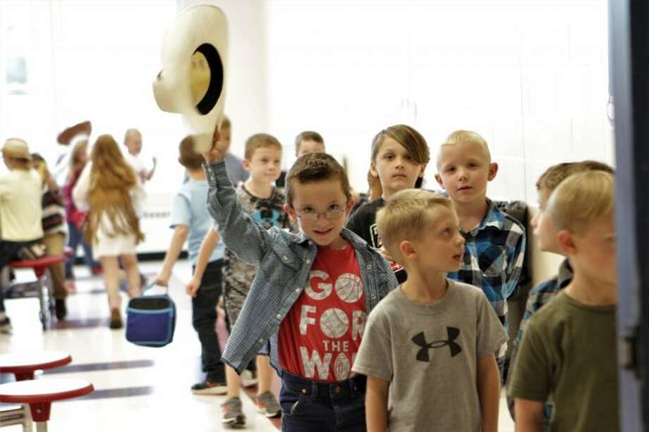 As G.T. Norman Elementary students finish their lunch on Country/Western Day, a youth stops to tip his hat for a photo. The dress-up day is one of the many planned through the week leading up to homecoming on Friday. (Herald Review photos/Meghan Gunther-Haas)