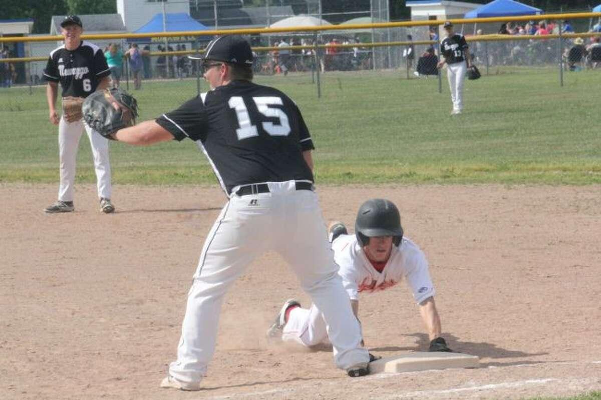 HE'S SAFE: Reed City's Hunter Morrison slides back into first base.