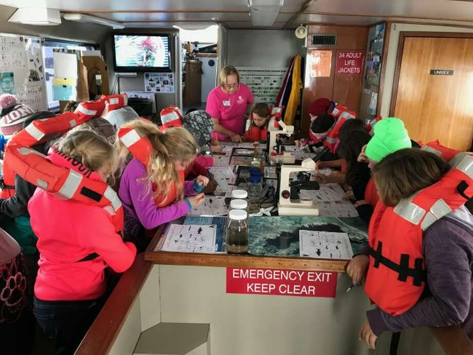 G.T. Norman Elementary fourth-graders gather around a table aboard a ship to study the water samples they took from Muskegon Lake and Lake Michigan during a field trip last week. (Courtesy photos)