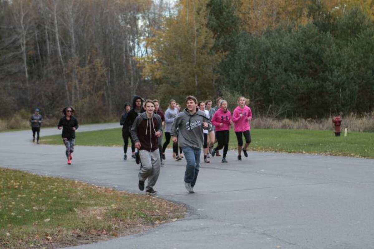 Members of the Marion High School cross country team run the final stretch of their 20-mile trek along the Pere Marquette Trail on Monday. Students ran to raise funds for the Susan P. Wheatlake Cancer Center. (Herald Review photos/Meghan Gunther-Haas)