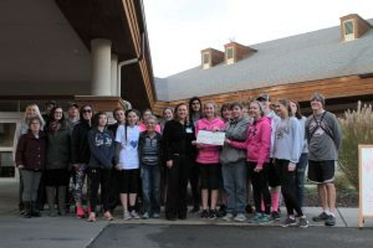 Runners, chaperones and cross country coach Jason Keeler stand with employees of the cancer center to present the check.