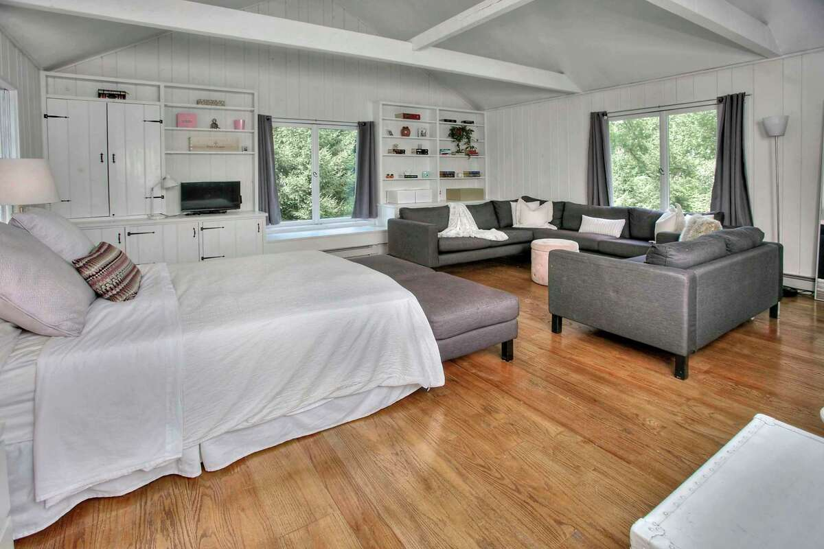 Above the attached two-car garage is a spacious bedroom with built-in shelving, window seat, a cathedral ceiling, and beams.