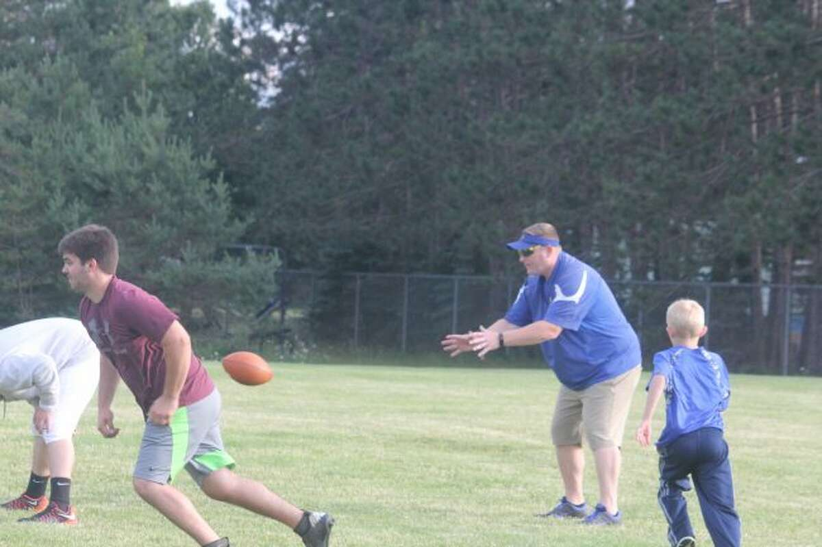 Evart football coach Pat Craven leads his team in a passing night on Sunday.