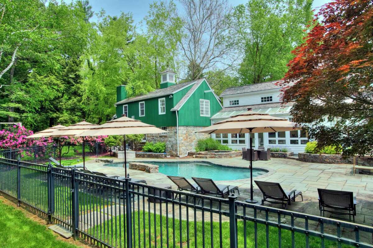 This house has an attached guest house, tennis court, and a heated Gunite in-ground swimming pool and spa.