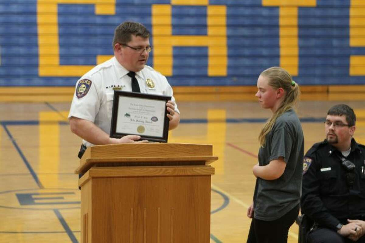 Evart High School senior Nichole Roys (right) stands as she is recognized for her quick thinking and actions on Tuesday, Dec. 4, when she performed the Heimlich maneuver on a choking fourth-grader. She received a plaque for her services on Thursday, Dec. 13, from Evart Police Department Chief John Beam. (Herald Review photo/Meghan Gunther-Haas)