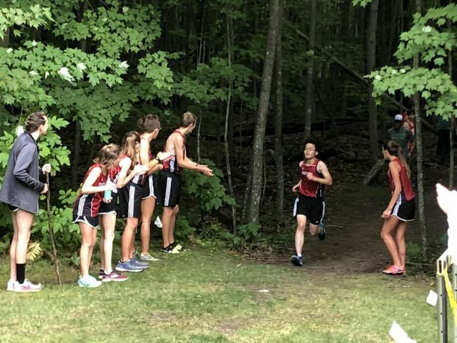 Reed City's Jackie Chan heads to the finish line at the Clare Invitational with fellow Coyotes cheering him on. (Herald Review file photo)