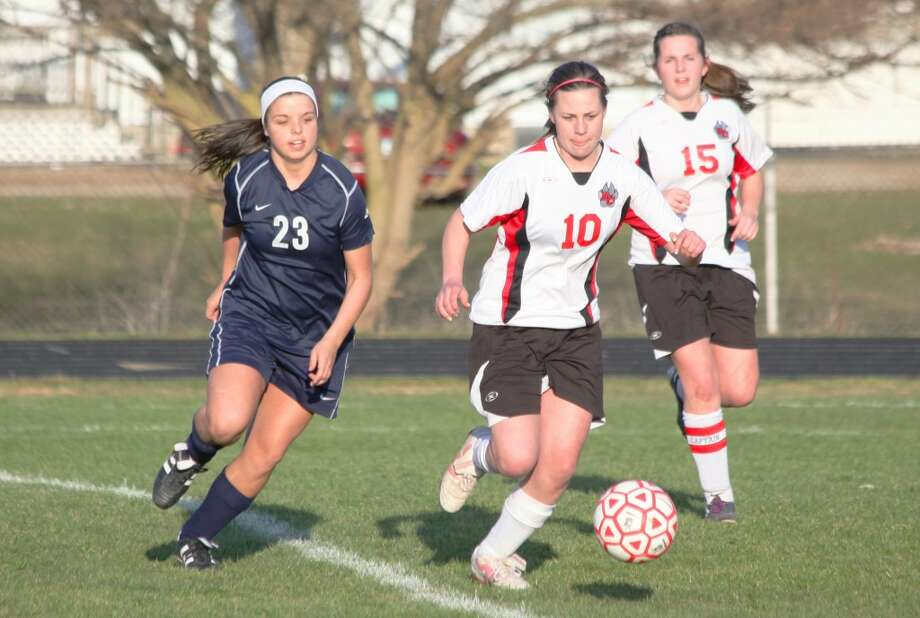 OPENING GAME: Reed City's Maddy Harrington (10) looks to dribble away from Lakeview's Danelle Wood during Monday's soccer action. (Herald Review photos/Greg Buckner)