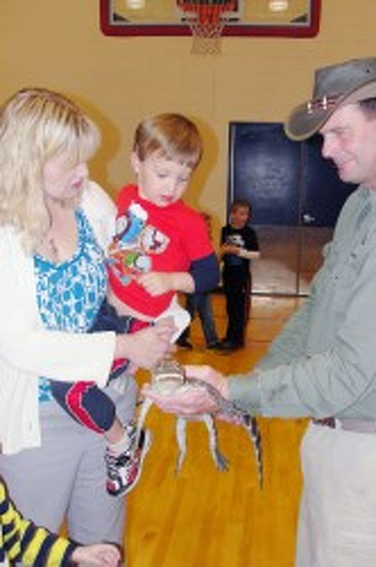 CREATURE ENCOUNTERS: Julie Hanson and her son, Ethan, get a visit from Oscar. In addition to little crocodiles, there were snakes, birds, and lizards on display. (Courtesy photo)