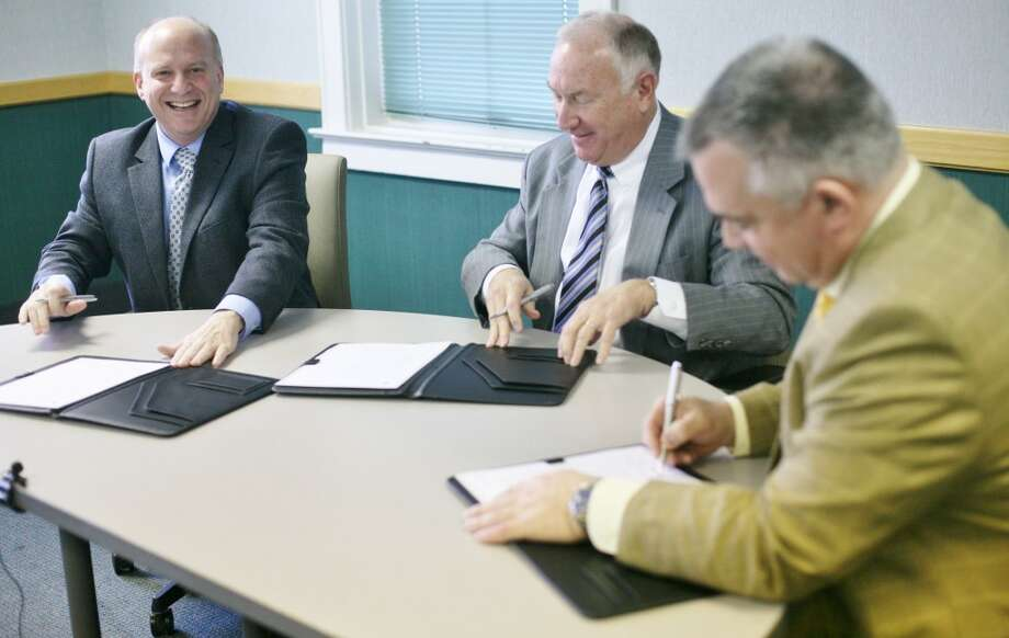 Mecosta County Commission Chair Eric O'Neil, Spectrum Health President and CEO Richard Breon and Dr. Fred Guenther, MCMC board chair, sign the merger agreement on Tuesday in MCMC's board room. (Pioneer photos/Whitney Gronski-Buffa)