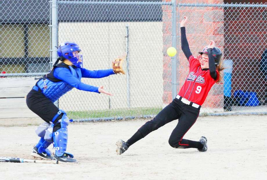 Sliding home: Skiler Brigham (9) of Reed City slides into home plate against MCC. (Herald Review photo Greg Buckner)
