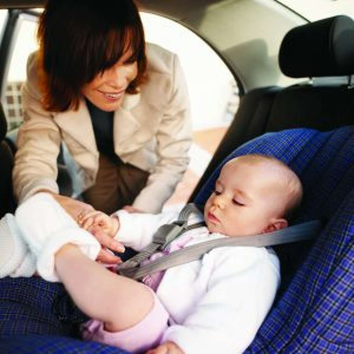 A woman buckles a child into a car seat in a vehicle. It's not only infants who are required to have a proper seat; a 2008 state law requires children in Michigan to be properly buckled in a car seat or booster seat until they are 8 years old or 4 feet 9 inches tall. (Courtesy photo)