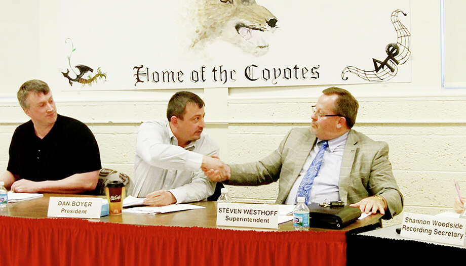 PARTING AGREEMENT: RCAPS board president Dan Boyer (center) shakes hands with superintendent Steve Westhoff after the board approved a retirement incentive for Westhoff on Monday. (Herald Review file photo)