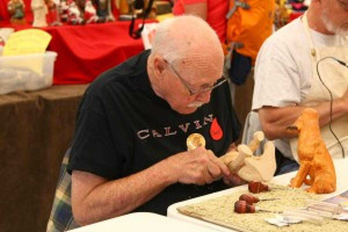 """OWIE: Art Wierenga, from the Jackson area, carves his way to a fully developed dog sculpture. Wierenga sported the """"Owie"""" pin, which is a lighthearted award given to the person first to draw blood while carving at the event. Although Wierenga received the pin, Evart Roundup Organizer Floyd Rhadigan joked that many accidents are not reported."""