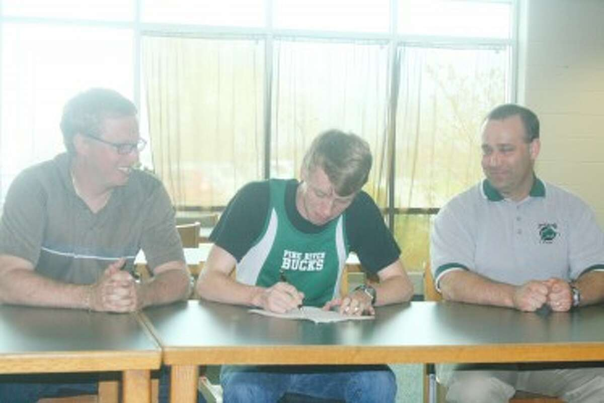 SIGNED FOR COLLEGE: Pine River coaches Eric Gebhard, left, of track and Ross Vrieze, right of crosscountry, watch as Trevor Holmes signs a letter of intent to attend Lansing Community College. (Herald Review photos/John Raffel)