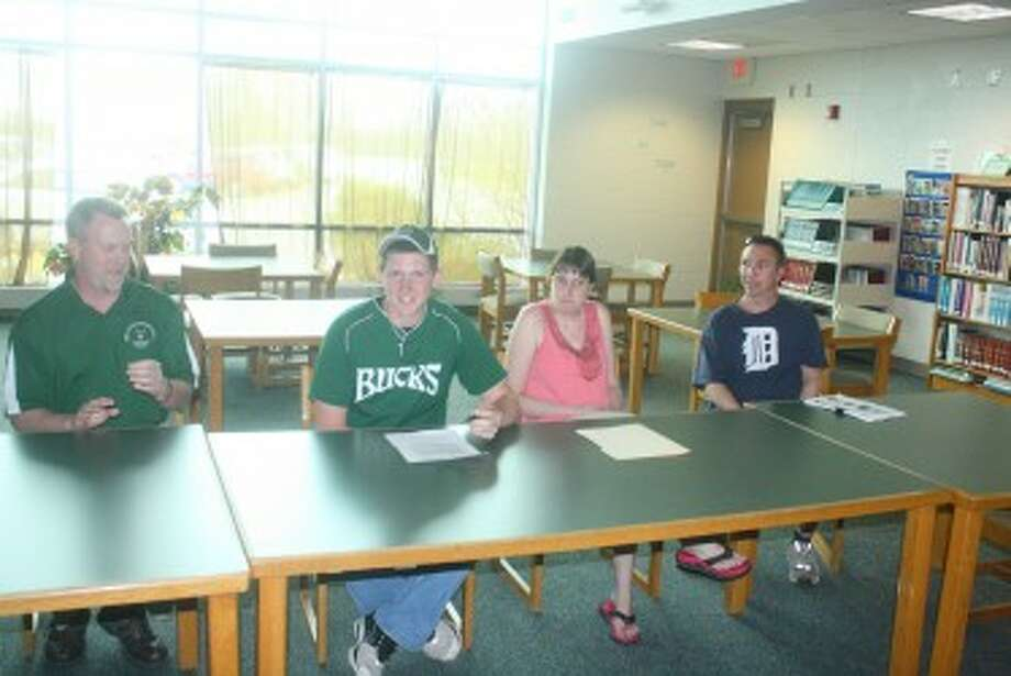 SIGNED ON: From left, Brian Goodenow, Pine Rive basetball coach, watches as Tyler Lewis signs a letter to attend Lansing Communtiy College where he'll play basketball. At right are his parents, Steve and Tiffany Lewis. (Herald Review photo/John Raffel)