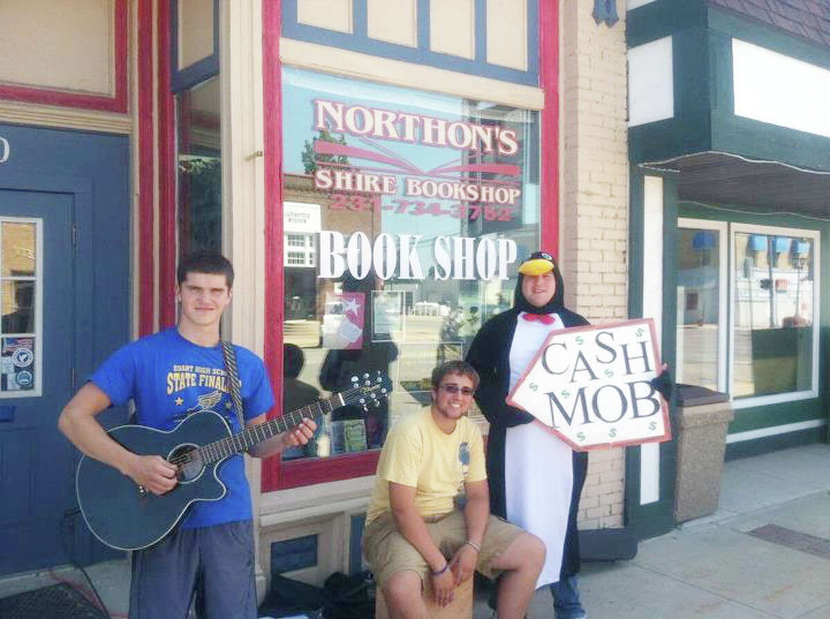 CashMob: Cash Mob Mondays volunteers (from left) Antonio Militello, AJ Weinberg and Chris Moore help draw people into Northon's Shire Bookshop with music during last year's event in Evart. This year, Cash Mob Mondays will begin on June 3 at B.C. Pizza.