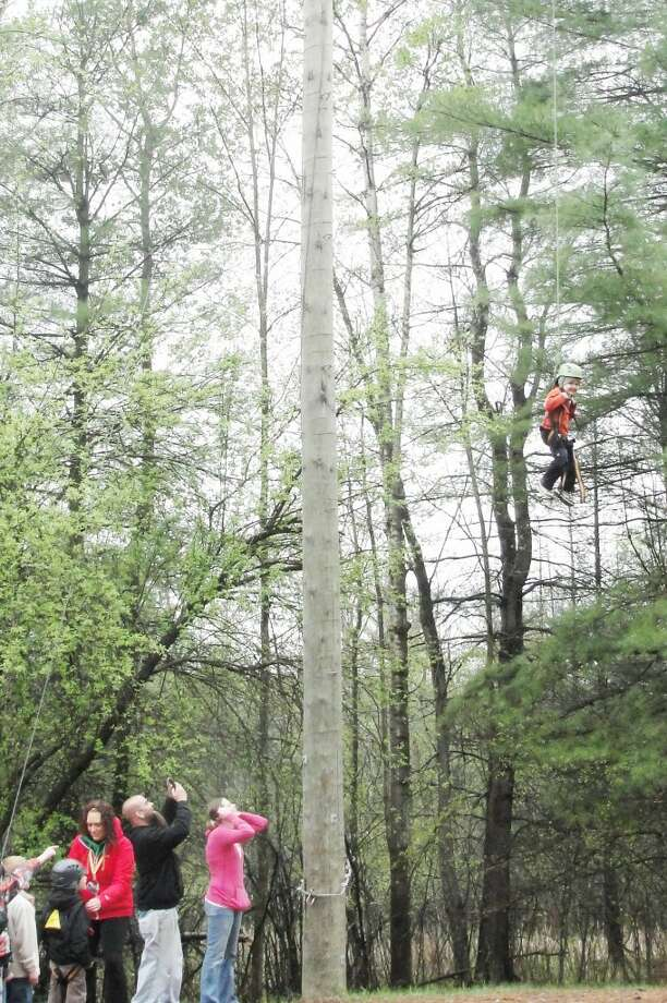 """day for adventure: Dominik Baker, age 5, is all smiles as he heads up 50 feet on the Flying Squirrel. When asked if he was scared at all, he just calmly responded, """"Nope."""" Raymond Penney. (Herald Review photos/Shannon Hartley)"""