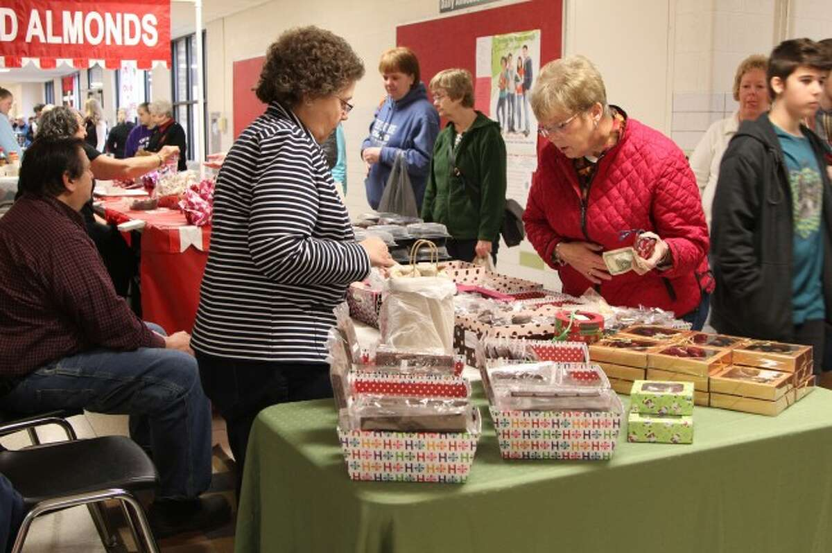 SHOPPING: Linda Stieg of Reed City stops to purchase some chocolate from a vendor during the craft show after also purchasing mittens and soap. Shoppers who attend the show, which will take place from 9 a.m. to 4 p.m. today at Reed City High School, will find hand-created products including knit items, woodworking pieces, home decor, jewelry, food and more.