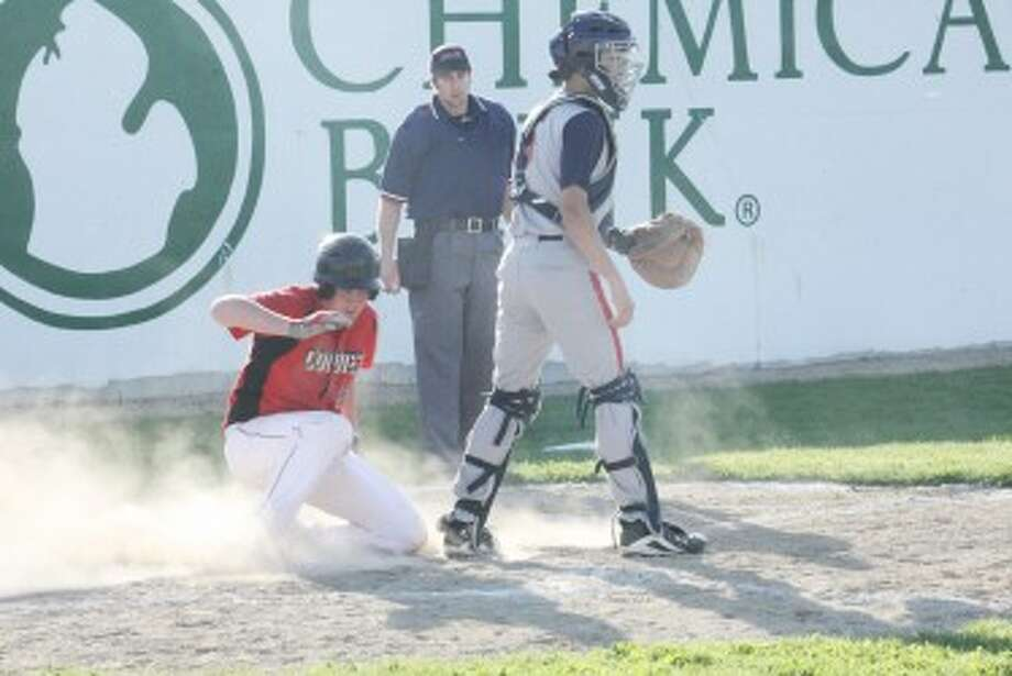 SAFE: Reed City's Ray Phenix slides in safe to home plate before Big Rapids' Tim Thebo gets a chance to apply a tag during Thursday's doubleheader. (Pioneer photo/John Raffel)