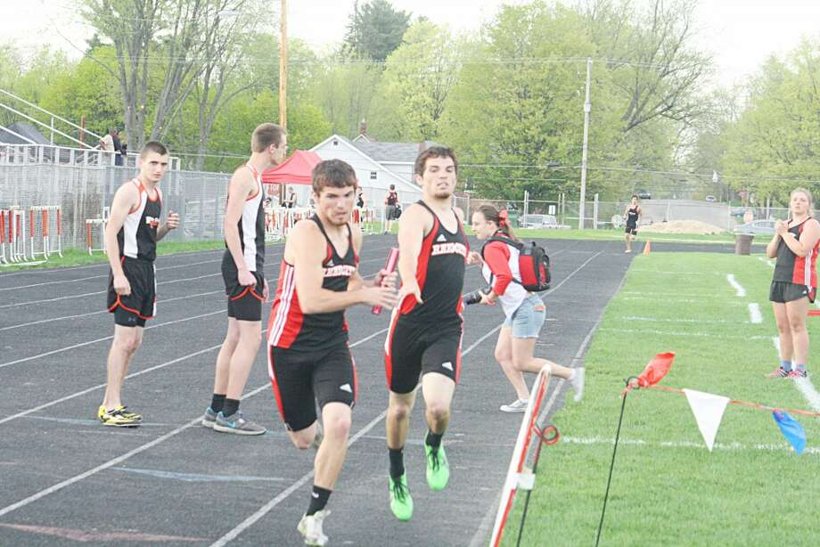 The hand off: Michael Bradford (front) gets set to take the baton from twin brother Eric Bradford in track action recently in Reed City (Herald Review photo/John Raffel)