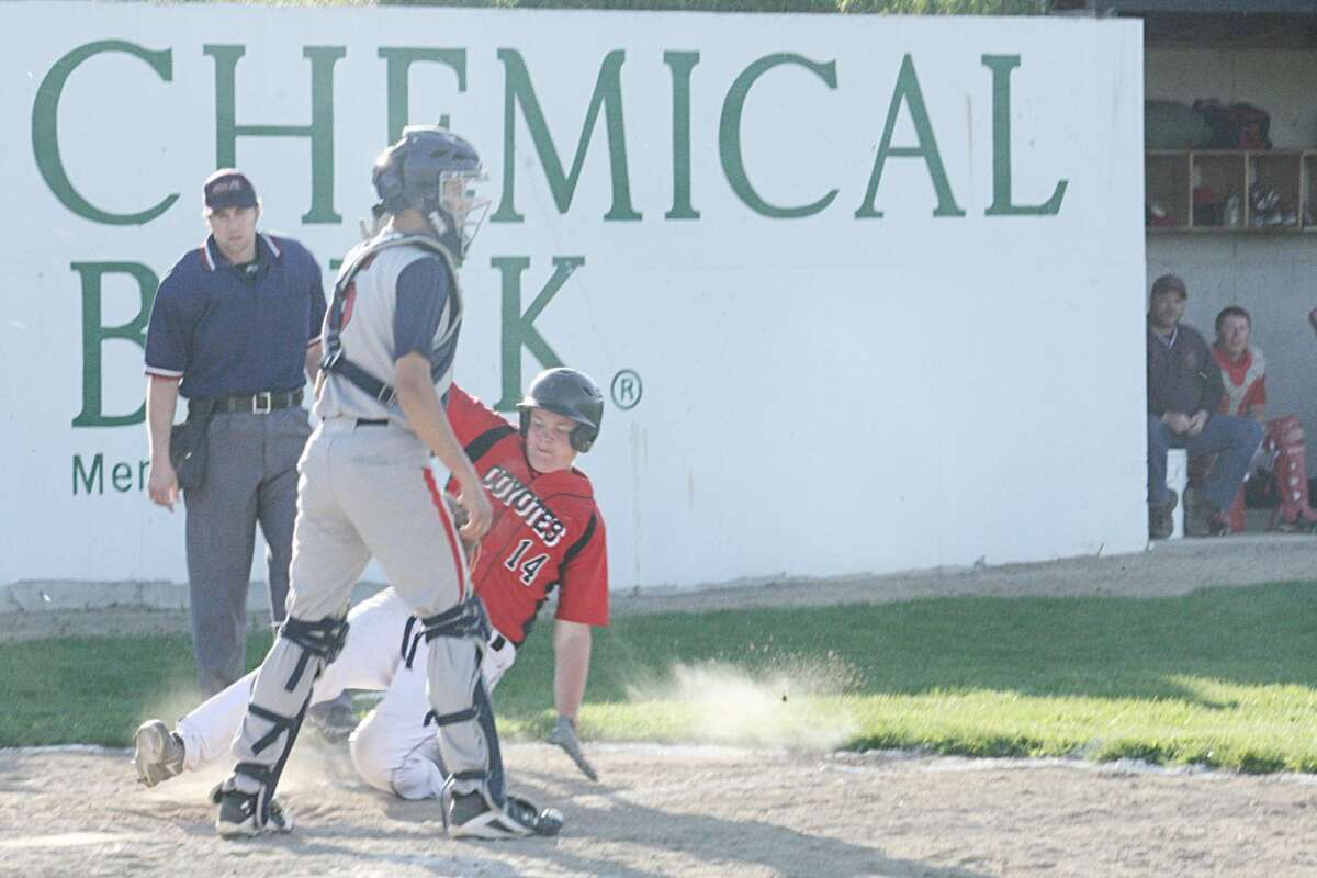 SLIDE: Ray Phenix (14) of Reed City slides into home plate. (Herald Review photo/John Raffel)