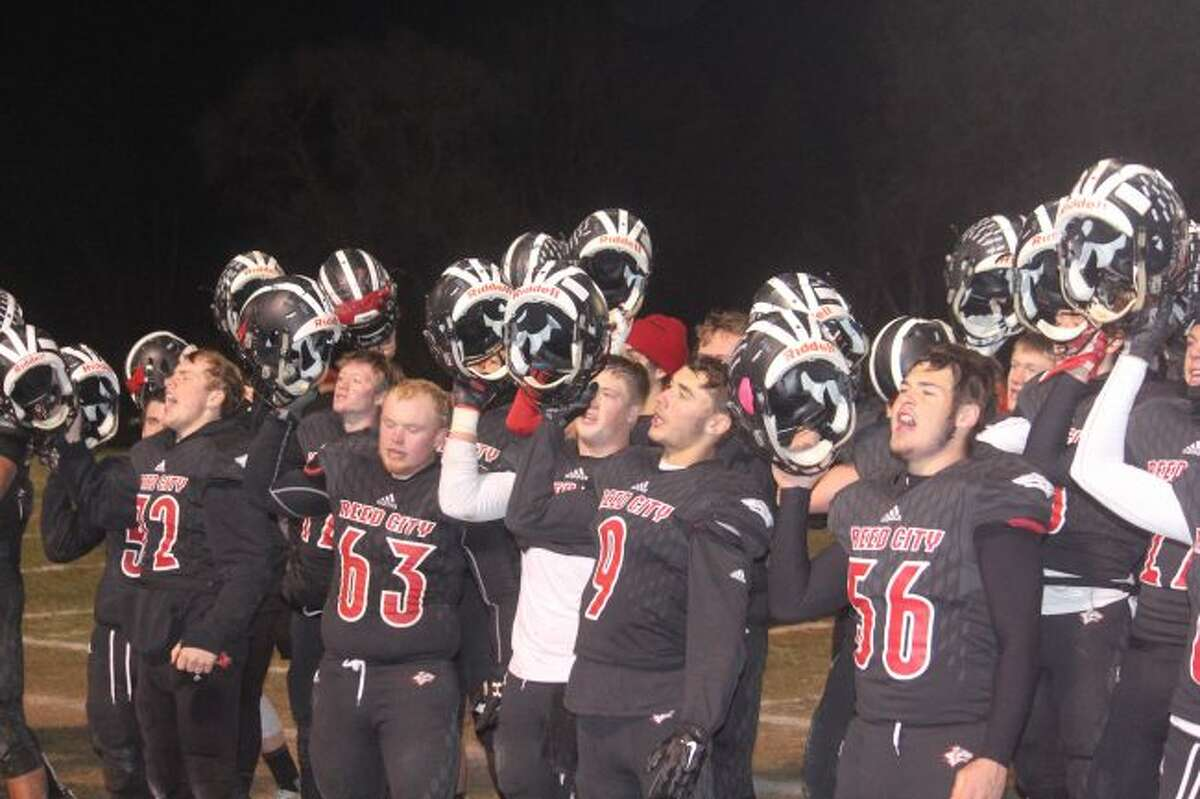 Reed City players sign fight song after taking regional title.
