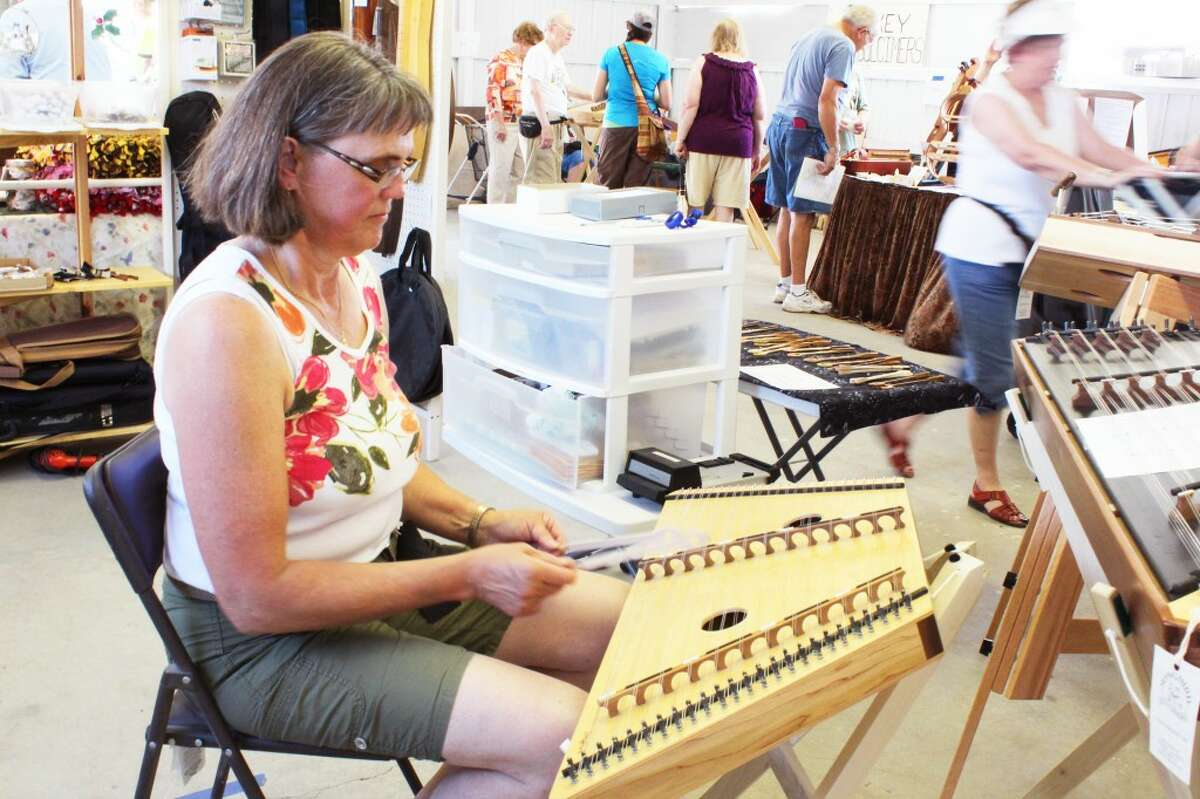 Fern Powers of northern Ontario, Canada, delicately plays on a hammered dulcimer she is thinking of purchasing. Powers is new to the dulcimer music world, discovering the instrument a few months ago and falling in love with its unique sound. She discovered the Dulcimer Funfest through the Internet and traveled to Evart for the occasion by herself.