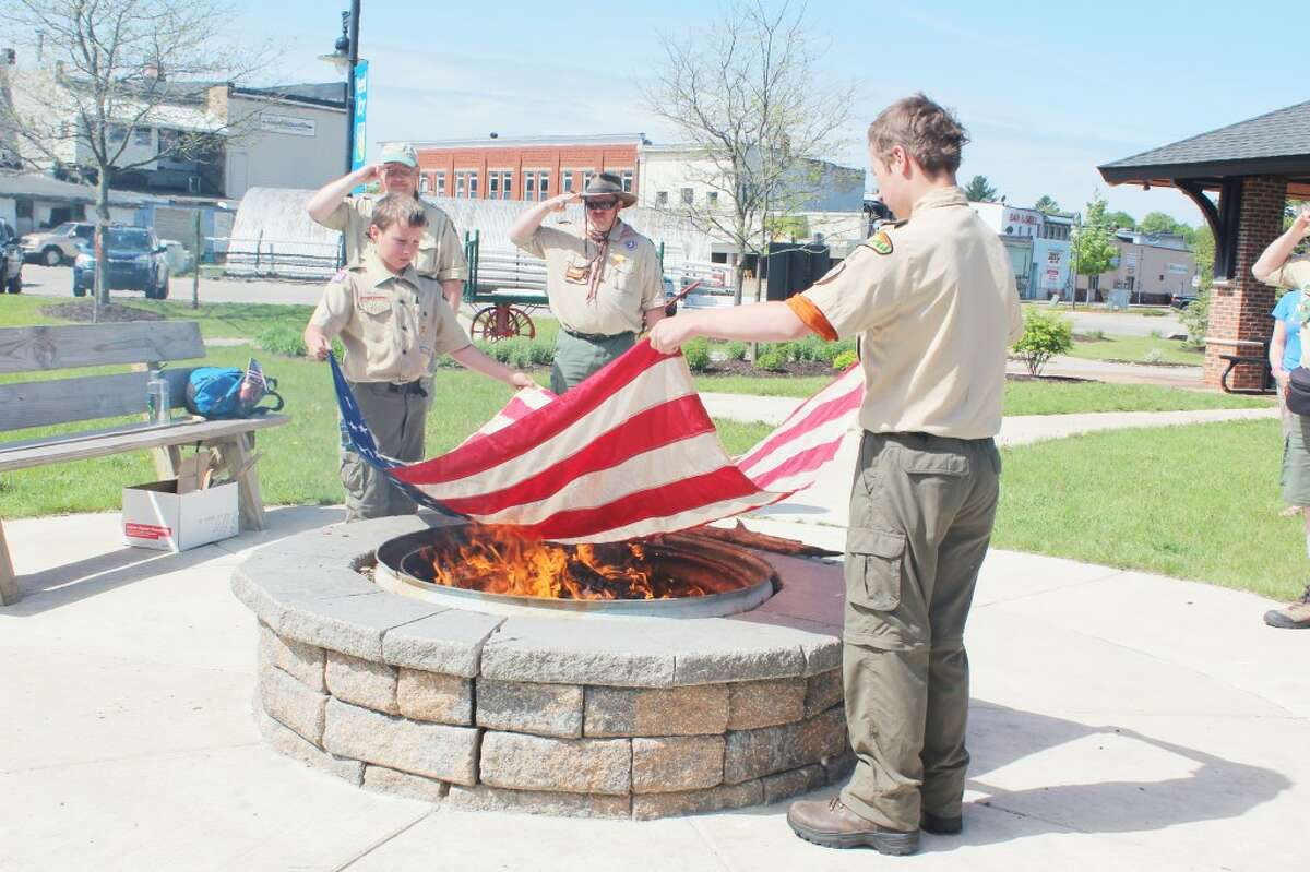 Honorable retirement: Members of Boy Scout Troop 74 perform a flag burning ceremony at the Reed City Depot. More than 10 flags were respectfully burned and saluted for their time serving as symbols of the country. (Herald Review photo/Karin Armbruster)