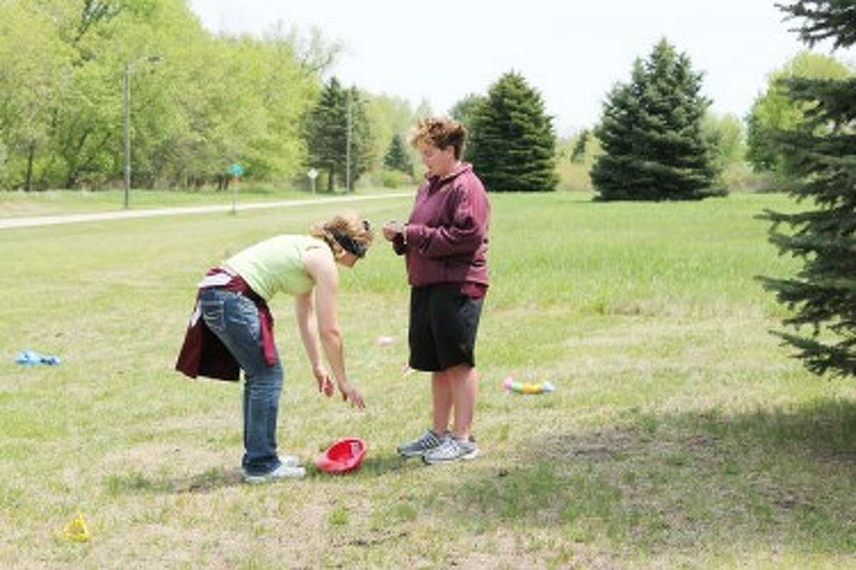 """Playing for their health: Also known as the team """"Treeville"""" Theresa Beeckman coaches Kris Spedowski in a blindfold challenge during the Heartchase event. (Herald Review/Shannon Hartley)"""