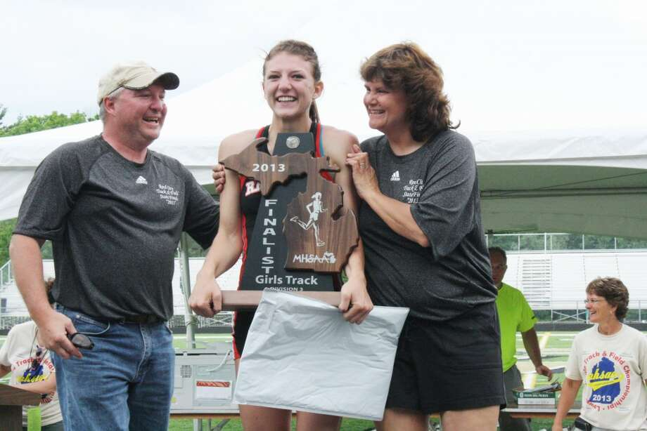 LEGENDARY: Reed City senior Sami Michell and her parents Brent and Vicki can't contain their excitement as Sami holds a second-place team trophy and the four state title medals she earned in her final appearance at the Division 3 state finals in Comstock Park Saturday. Michell set the new career state title record by ending her career with 12 individual titles after winning four titles for the second consecutive year on Saturday. (Herald Review photo/John Raffel)