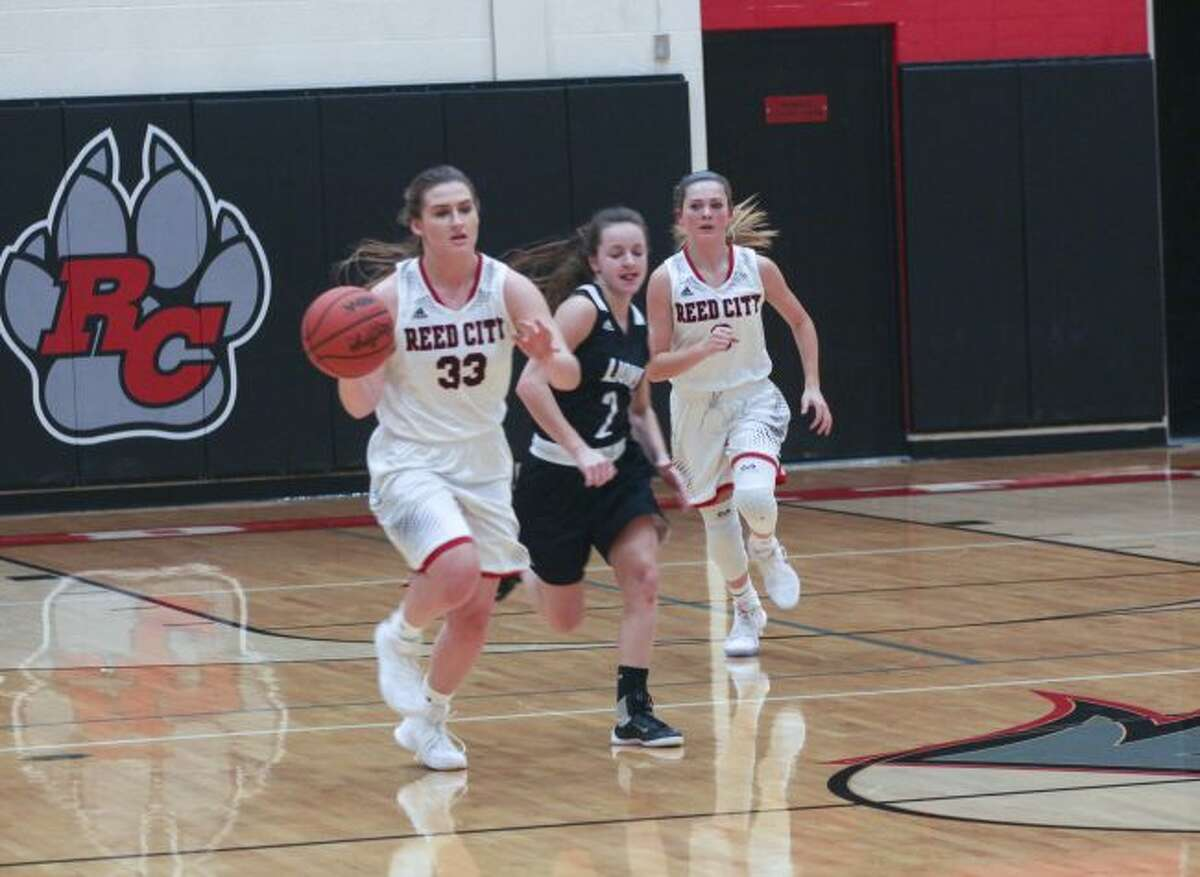 Emily Libey (33) heads up the court for Reed City.
