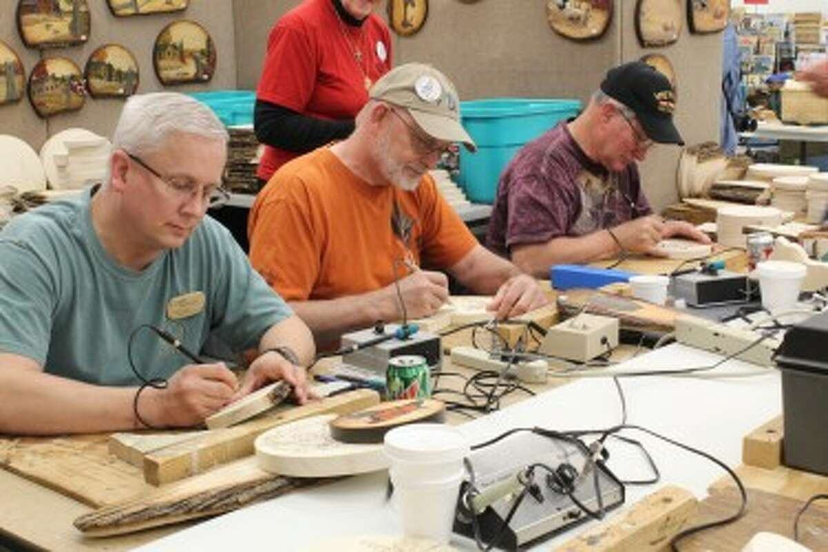 WOODCARVERS ROUNDUP: Members of the Grand Valley Wood Carvers out of Ionia partake in wood burning projects in one of many workshops going on simultaneously during the Evart Roundup, which will take place through Saturday. This is the 15th year of the event, which brings in hundreds from across the United States.(Pioneer photos/Karin Armbruster)