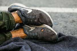 Homeless man Kevin Christopher Highfield's, 39, shoes are seen as he tries to rest in a parking spot on Larkin Street in San Francisco, California, on Tuesday, June 18, 2019. Kevin said he has been homeless since he was 18 years old after getting kicked out of the house by his mother. He broke his left leg and it never properly healed so it causes him great pain.   Photo taken on Larkin Street between McAllister and Fulton Streets at 7:08pm