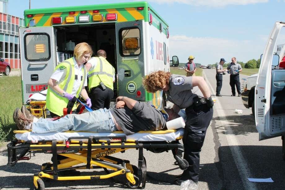 """A life saving role: Life EMS Ambulance, Osceola County EMS personnel and township first responders help a """"victim"""" during a simulated crash scene on Friday on Old U.S. 131 in Reed City. The scenario was part of a training exercise with Spectrum Heath Reed City Hospital. (Herald Review photo/Karin Armbruster)"""