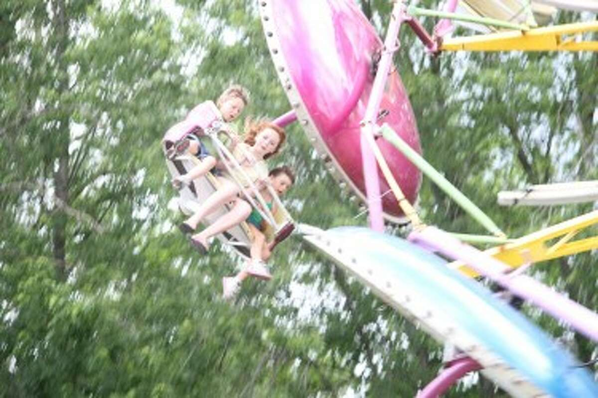 Three children enjoy riding one of the many midway attractions at last year's Marion Fair. This year, rides, grandstand events and much more will take place from Sunday through June 29 in the village. (Herald Review file photo)