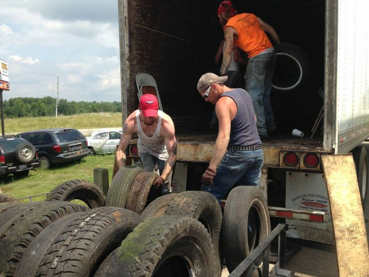 TIRE DISPOSAL: Four inmates from the Osceola County Jail helped residents load their unwanted tires onto the semitrucks during the third annual tire round-up which took place on dates in June and July. (Herald Review photo/Randy Johnston)