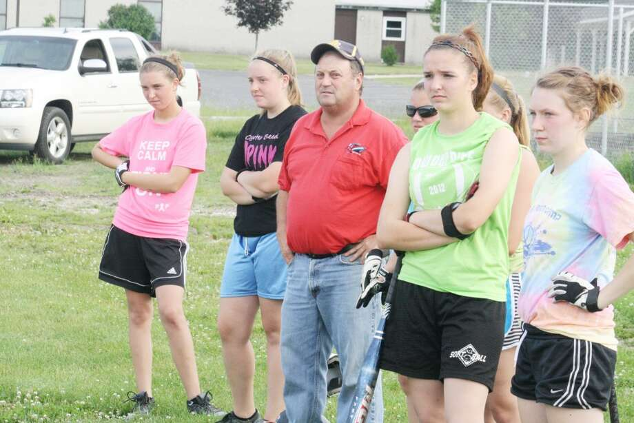 Summer Practice: Roger Steig and his Reed City softball players watch a hitting demonstration on Sunday. (Herald Review/John Raffel)
