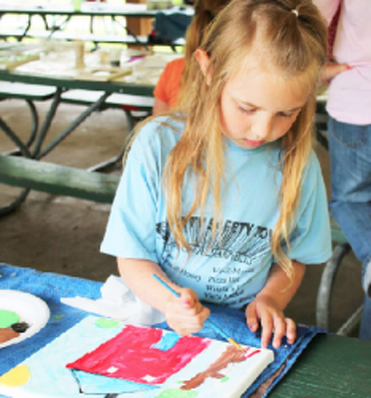 perfecting her art: Lauren McCarver, 7, has become quite a regular at Art in the Park. She enjoyed painting her family home. (Herald Review/Shannon Hartley)